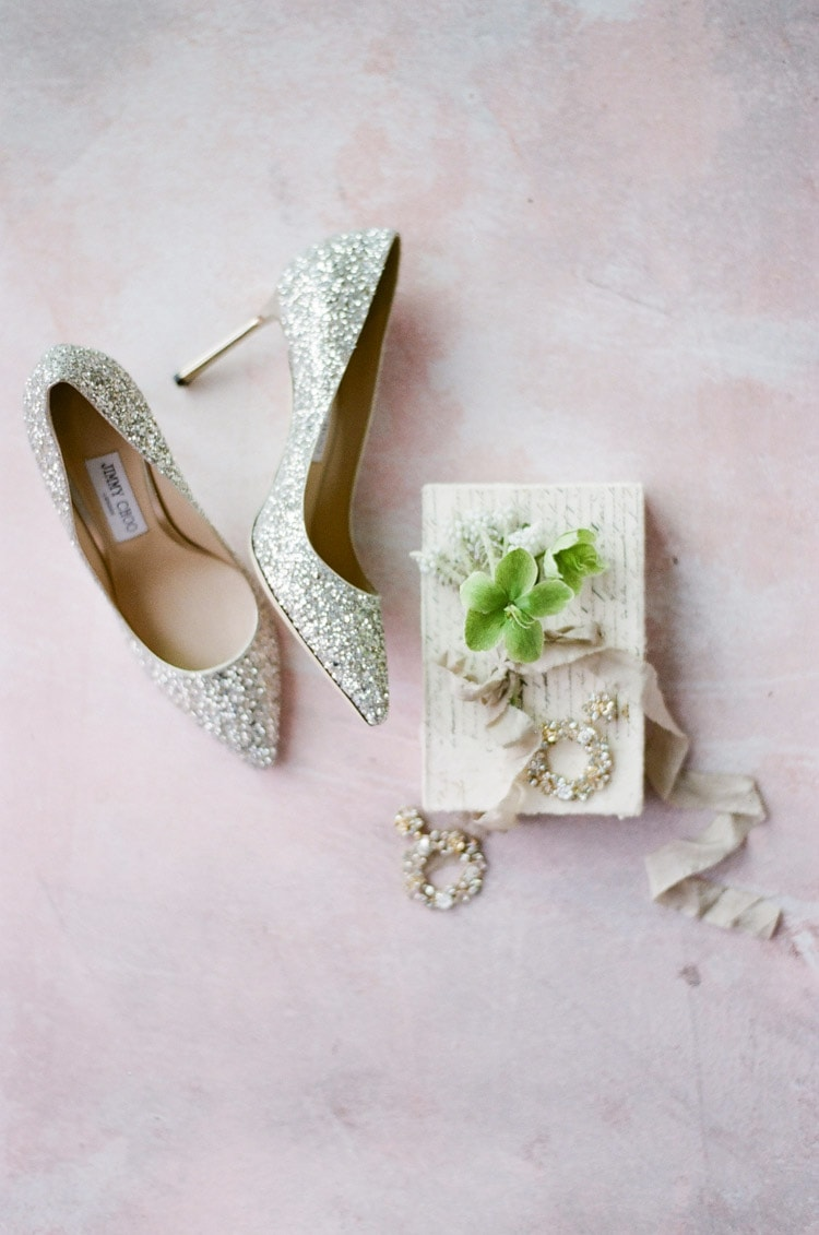 Sparkly silver high heels against a pink backdrop
