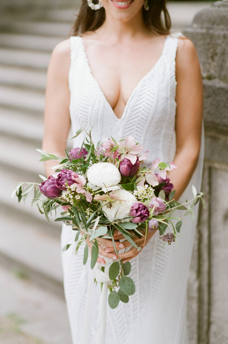 Bride holding bouquet in shades of wine and white with greenery