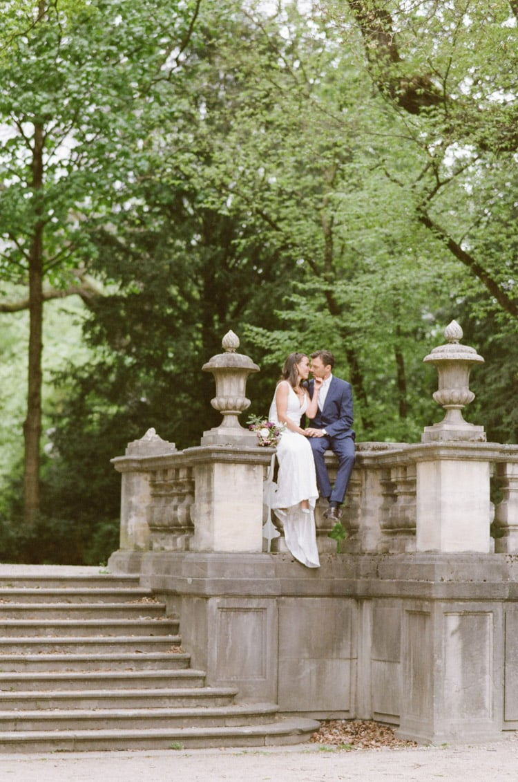 Bride and groom sitting on a railing in Munich