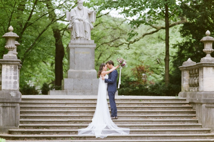Bride and groom standing on steps in front of a statue in Munich