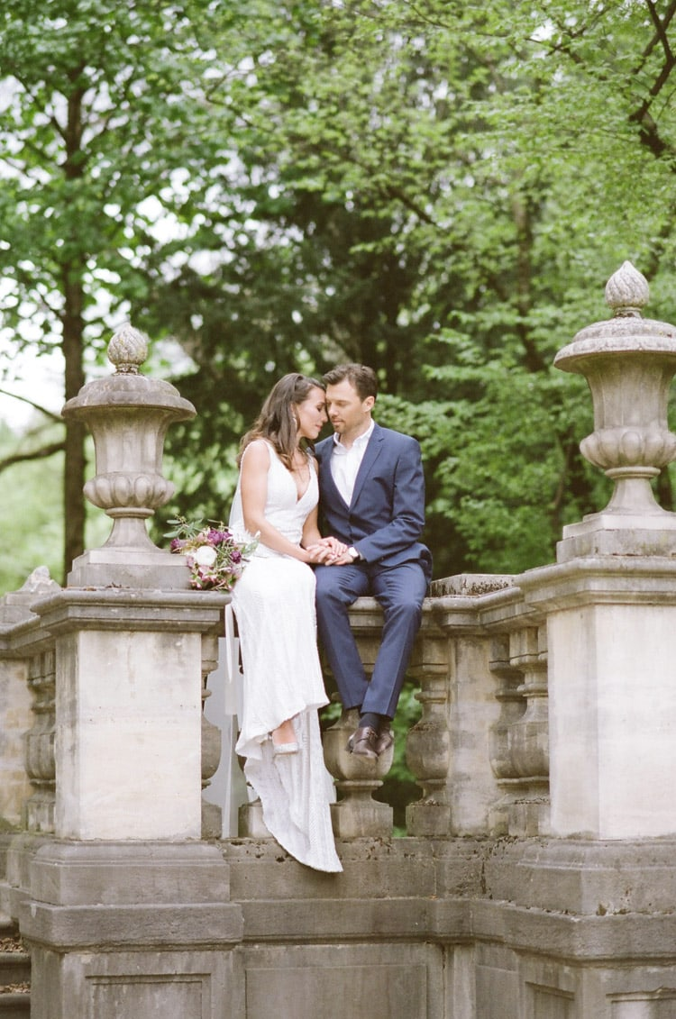 Bride and groom sitting on stone railing in Munich