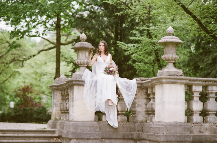 Bride sitting on old stone railing in Munich