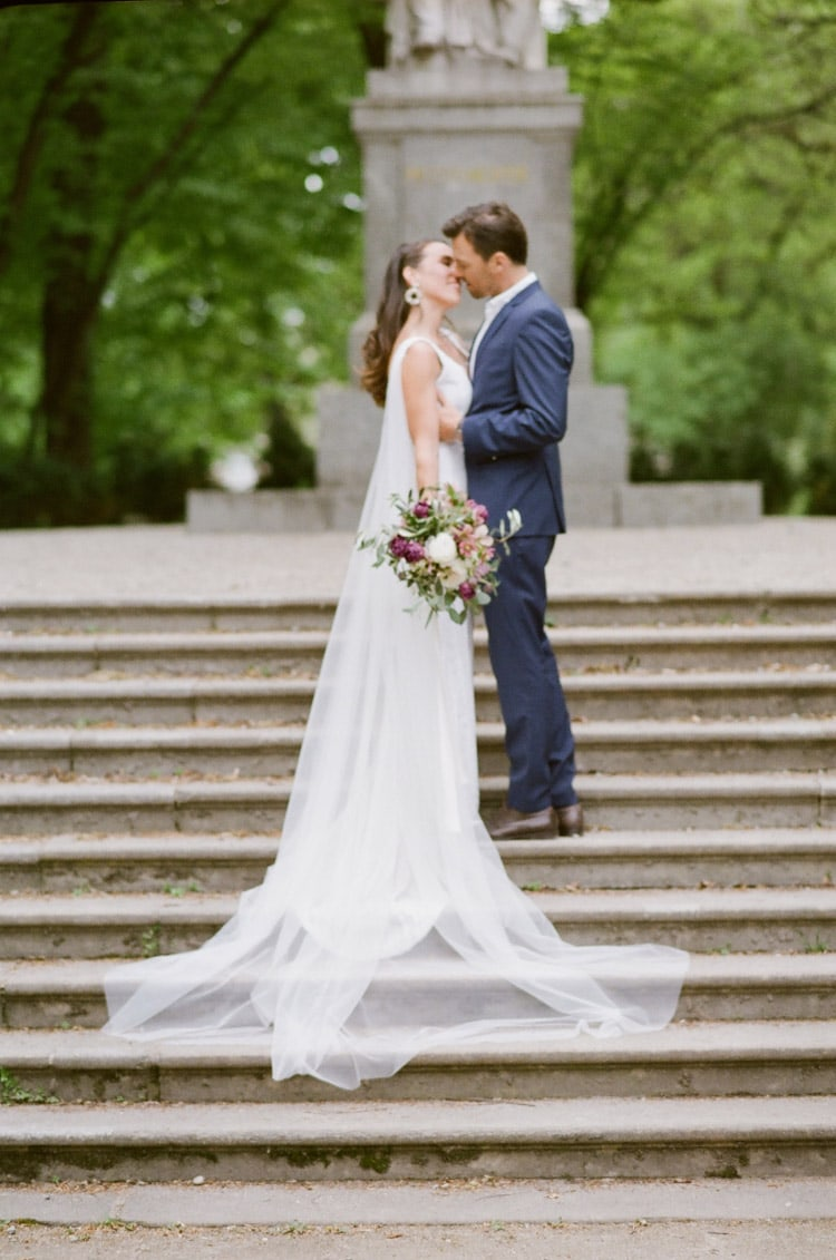 Bride and groom kissing on steps in Munich