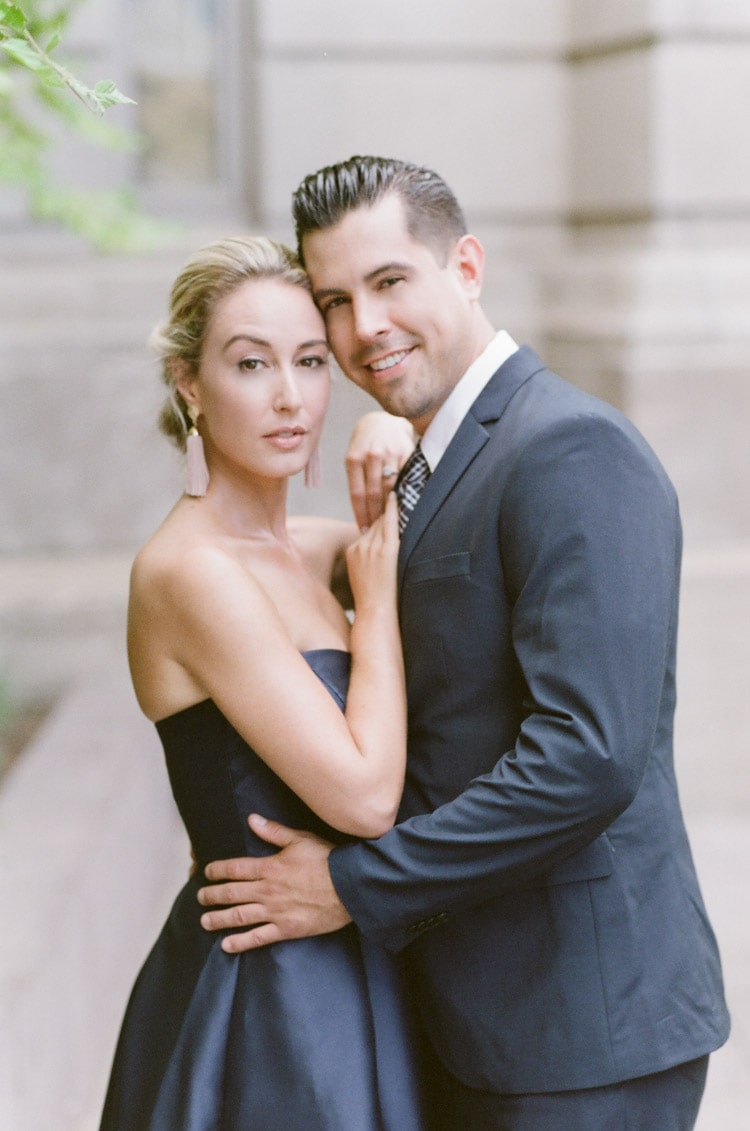 Woman with serious look and man smiling while embracing eachother