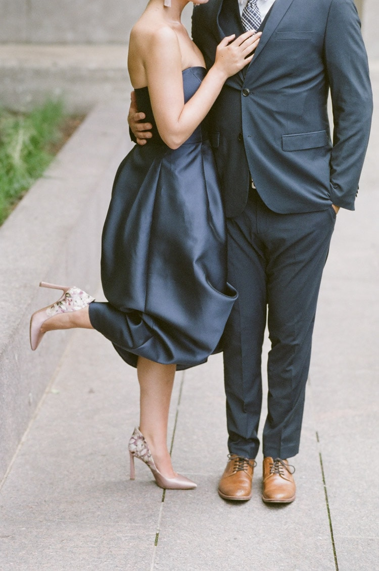 Couple's navy blue outfits with blush high-heels and tan dress shoes