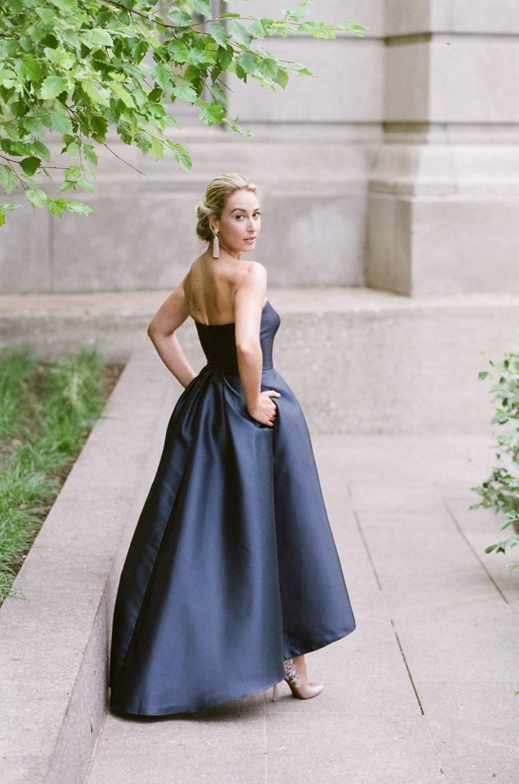 Woman looking over shoulder wearing a strapless navy blue evening dress in Chicago