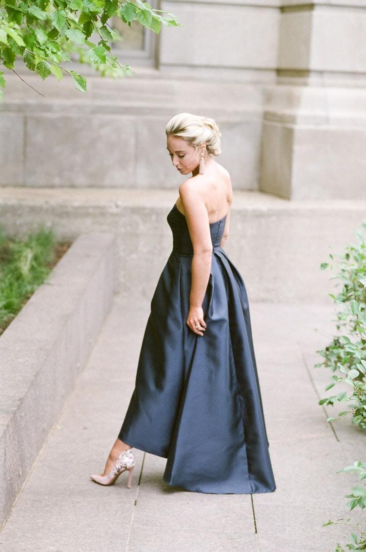 Woman in navy blue dress looking down