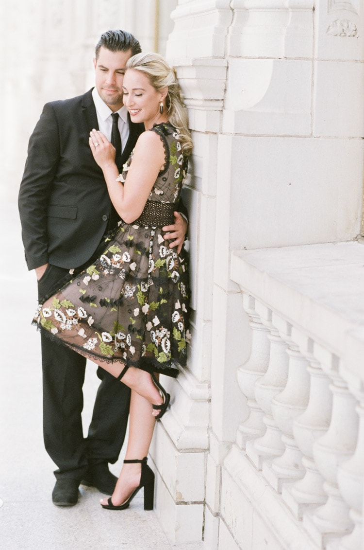 Couple leaning against white stone wall wearing black suit and black floral mini dress