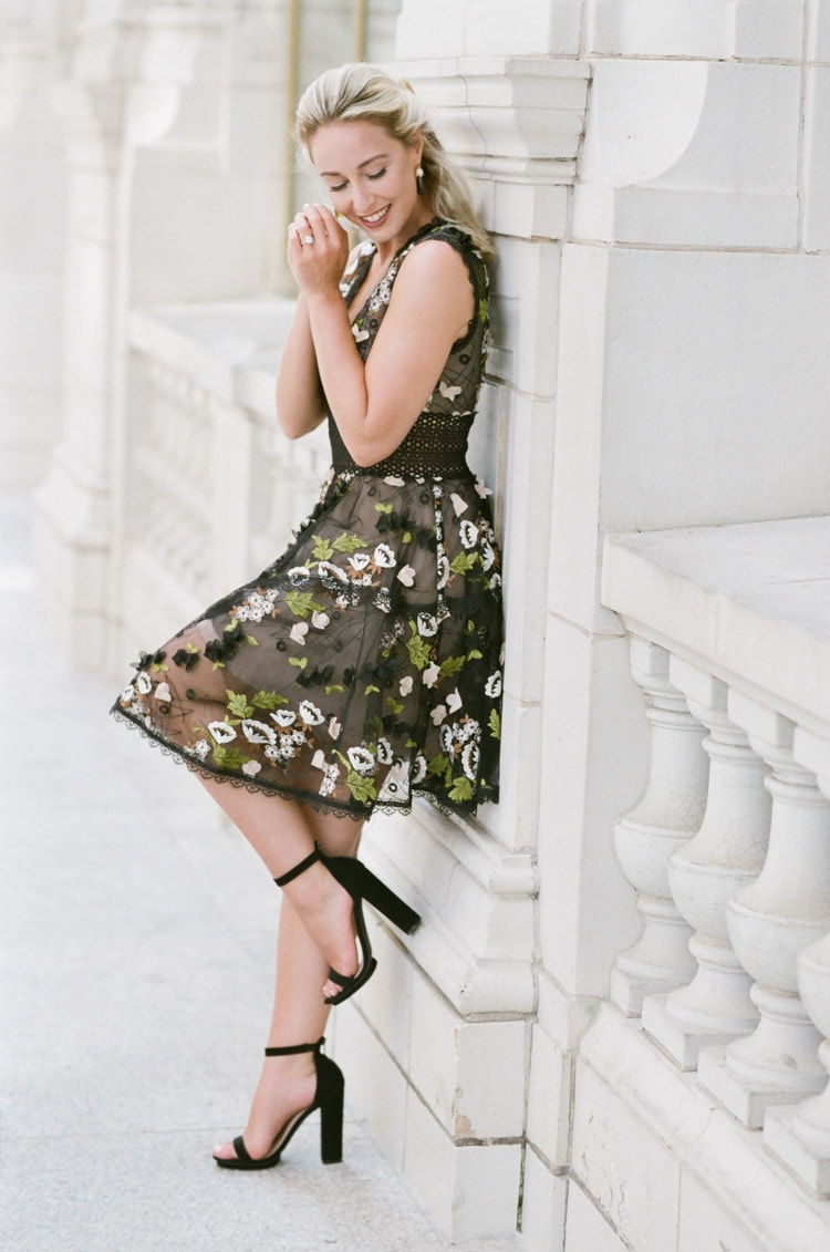 Woman wearing black mini dress with colorful floral embroidery and black heels up against stone white wall