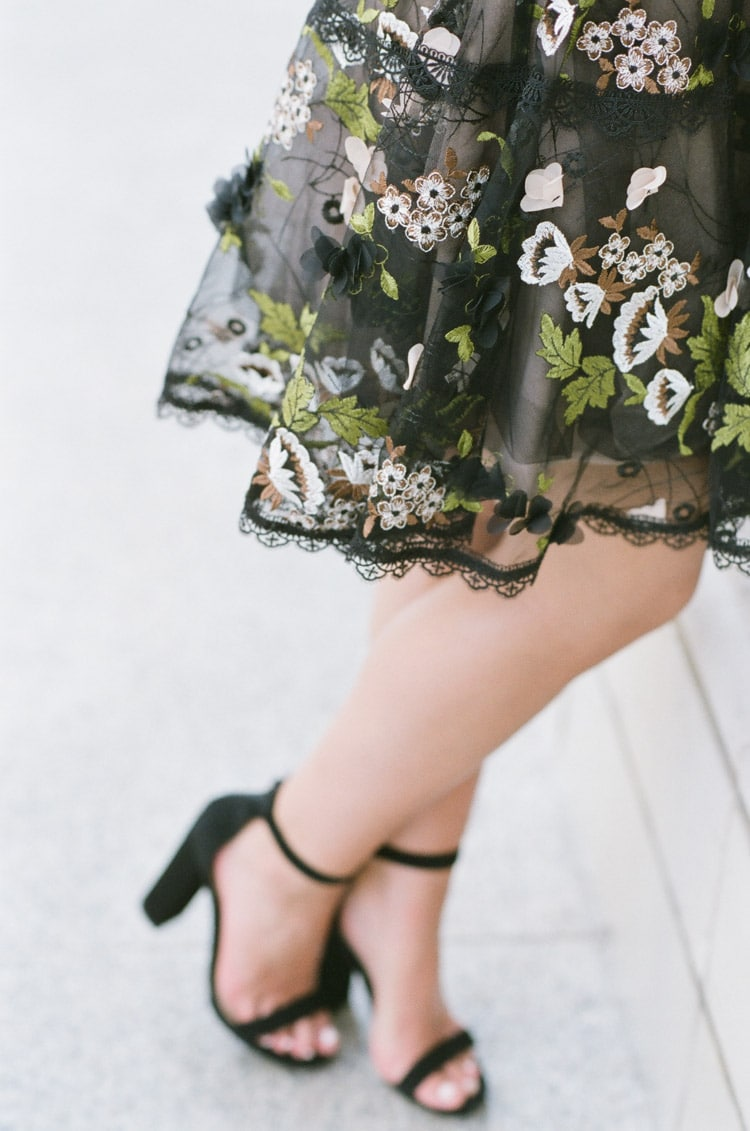 Bottom half of black mini dress with colorful floral embroidery and black heels