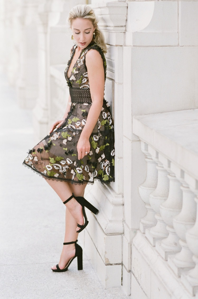 Woman looking down wearing black mini dress with colorful floral embroidery and black heels up against stone white wall
