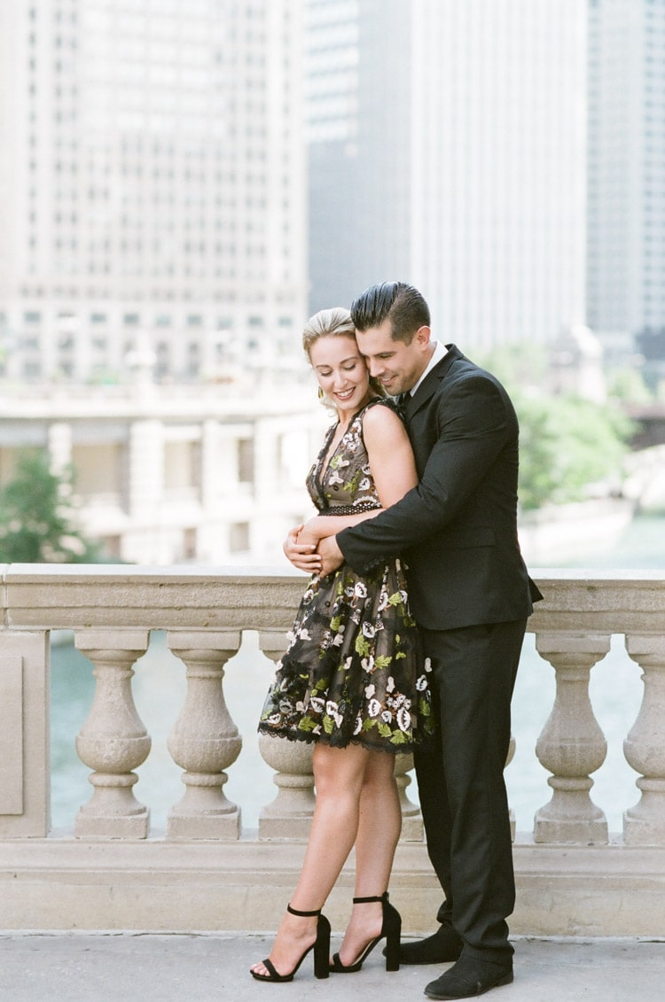 embracing with view of Chicago Riverwalk over the stone white railing