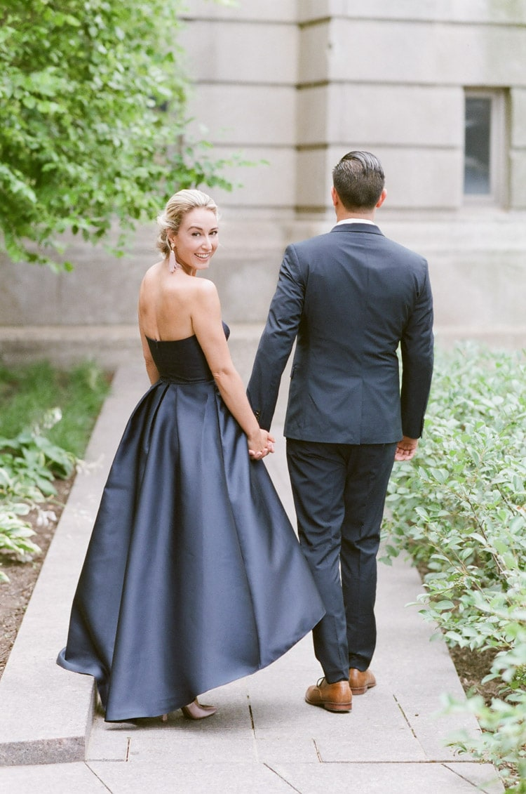 Couple holding hands while walking down Chicago Riverwalk during their engagement portrait session