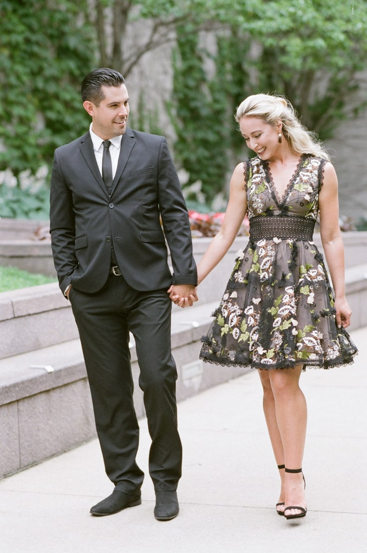 Couple casually walking while holding hands and smiling