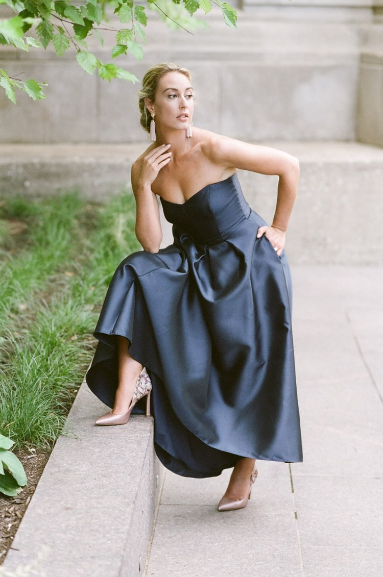 Woman posing while wearing a strapless navy blue evening dress in Chicago