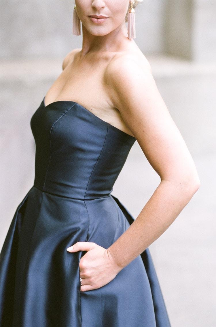 Closeup of woman wearing a strapless navy blue evening dress