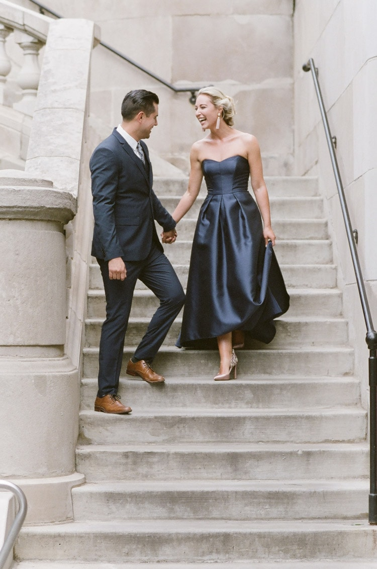 Engagement couple walking down outside stairs holding hands