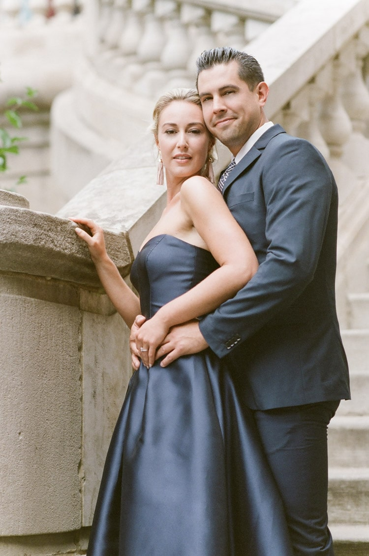 Couple in navy blue colored outfits outside next to stairs