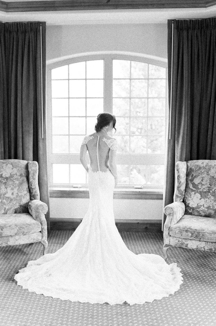Black & white of back of bride wearing lace Ines Pi Santo dress