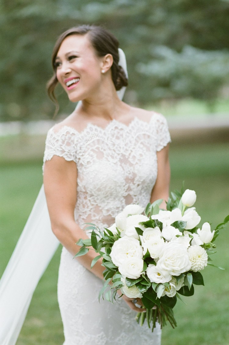 Timeless look of bride smiling wearing lace Ines Pi Santo dress holding bouquet