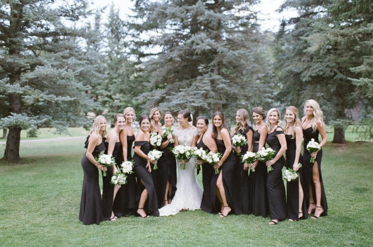 Bride in white posing with bridesmaids in black