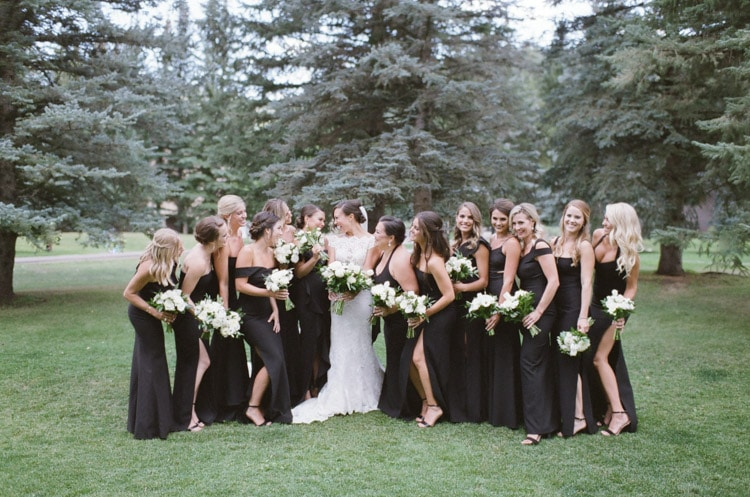 Bride & bridesmaids holding white bouquet of flowers while laughing