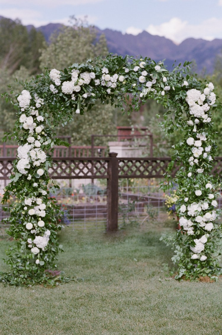Outdoor ceremony with classic arch showing shades of white and green