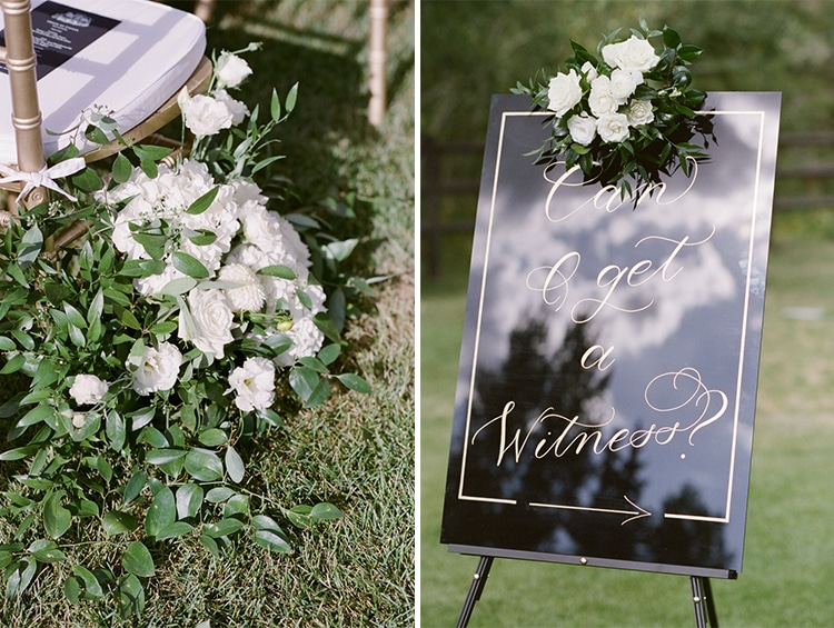 "Large decoration of white flowers and greenery next to chair on left side. Black sign with white calligraphy that says ""can I get a witness' on the right"