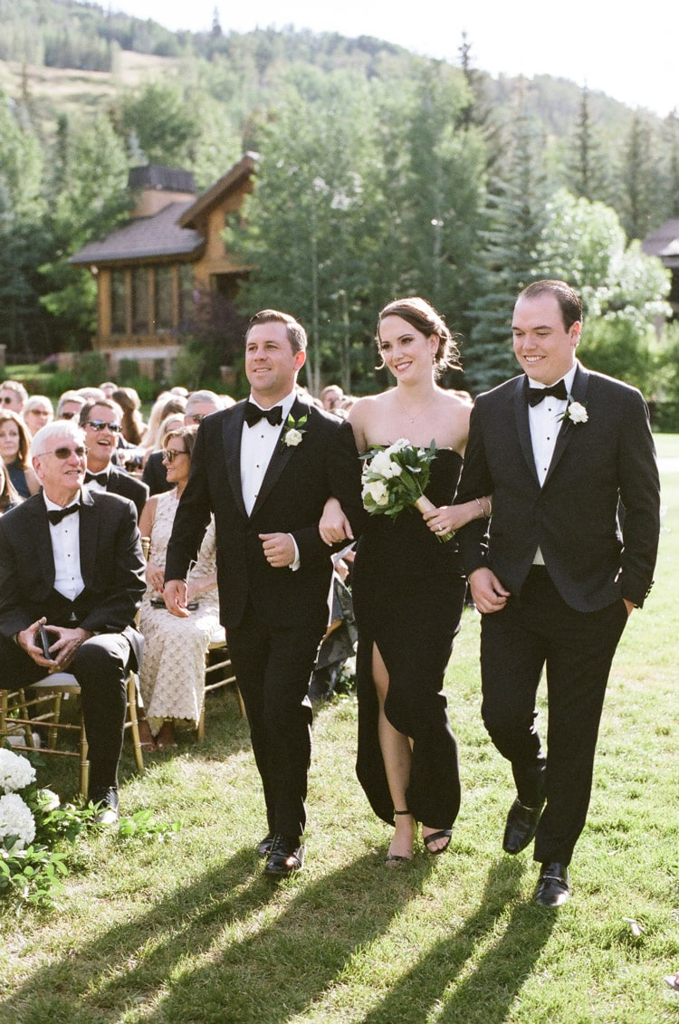 Procession of bridesmaids and groomsmen walking down the aisle