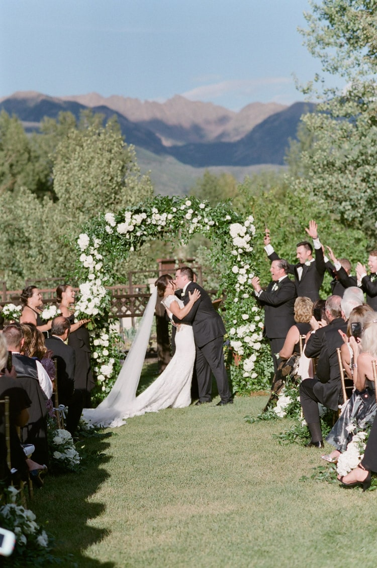 First kiss at ceremony underneath floral arch with mountain backdrop