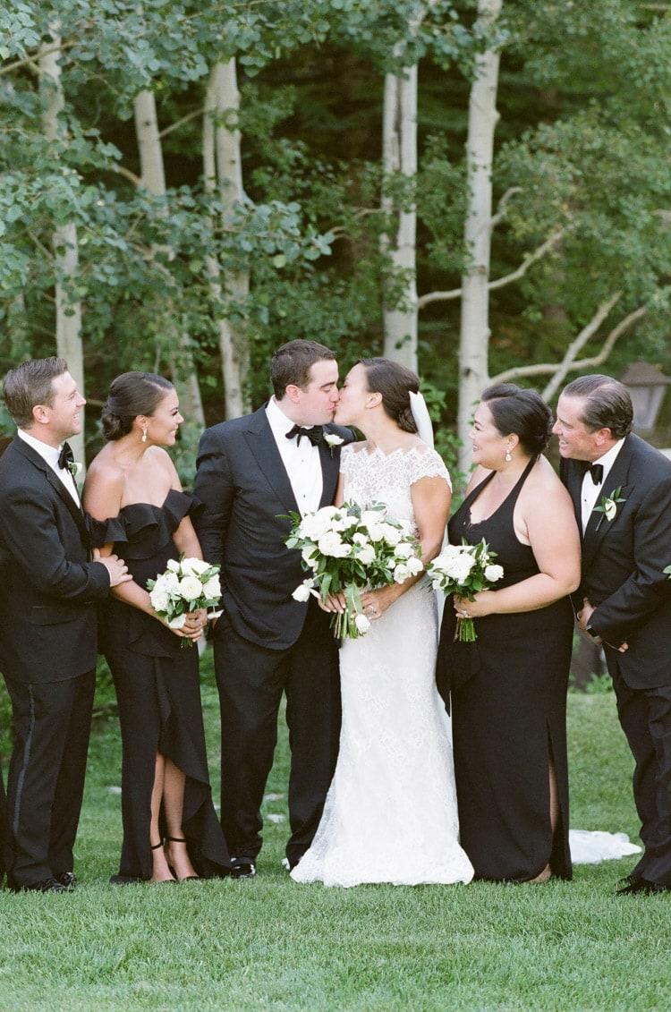 Married couple kissing in between bridal party
