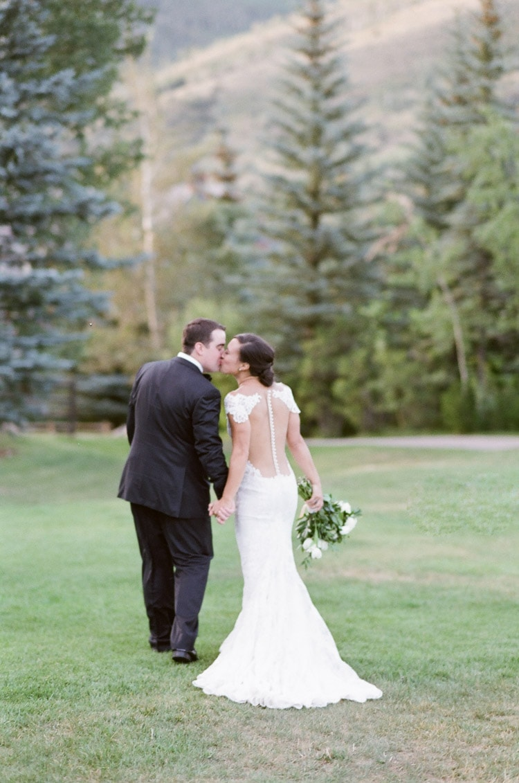 Bridal couple facing away kissing on grass and pine tress in backdrop