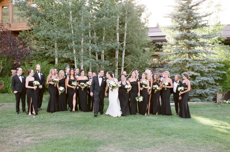 Bridal party together after ceremony on lawn in front of aspen trees