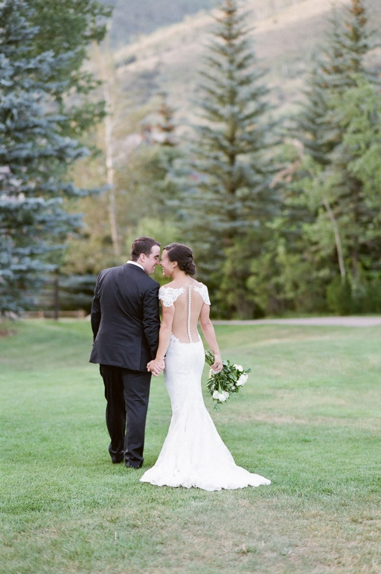 Bridal couple facing away with foreheads touching on grass and pine tress in backdrop