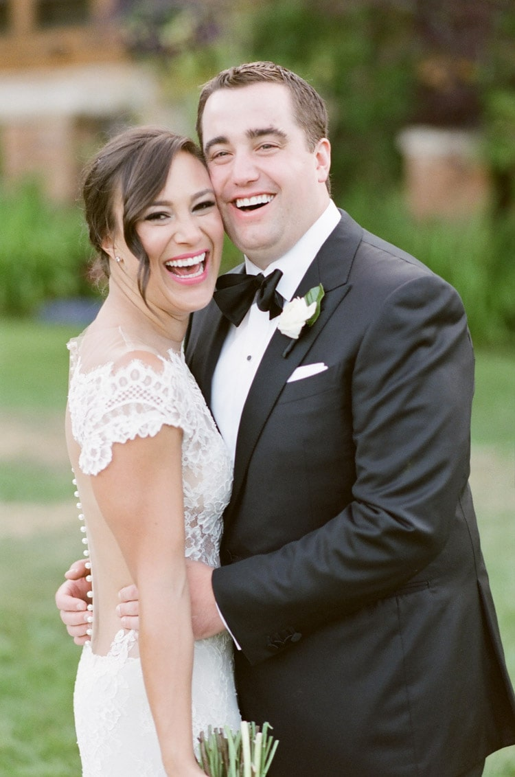 Smiling couple with groom complimenting bride's look with sophisticated black tuxedo