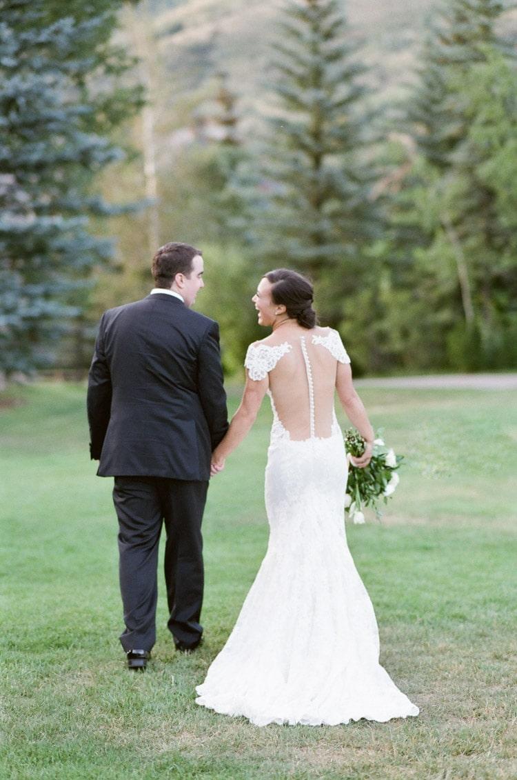 Bridal couple facing away walking on grass