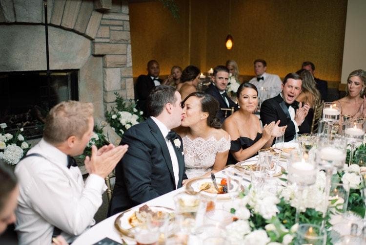 Groom & bride kissing at wedding reception