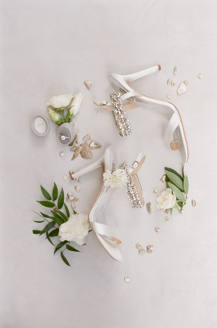 Styled shot of bride's sparkly Badgley Mischaka shoes and surrounded decorations