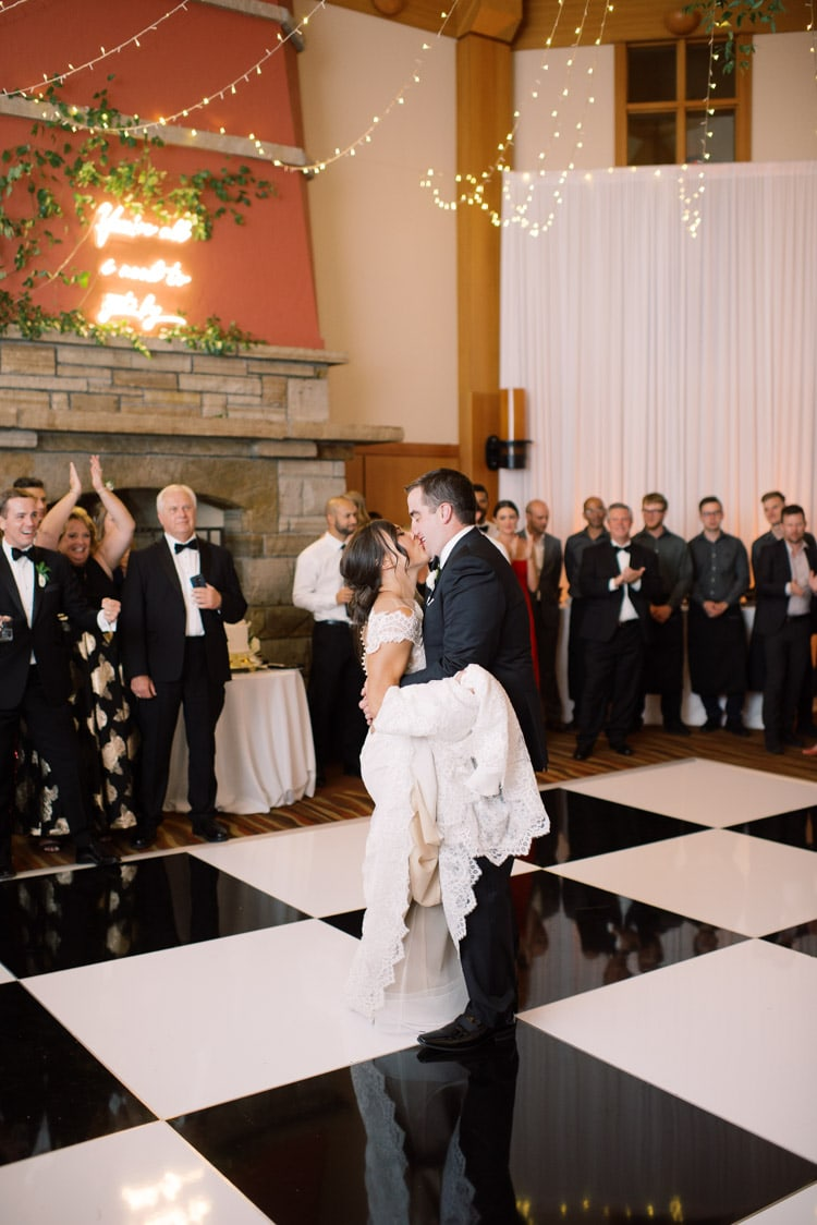 Kissing at first dance with black & white checkered dance floor pattern