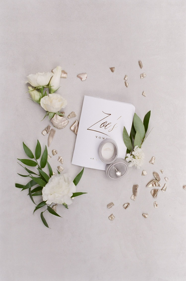 Custom wedding stationary with wedding ring in case and surrounding white flowers