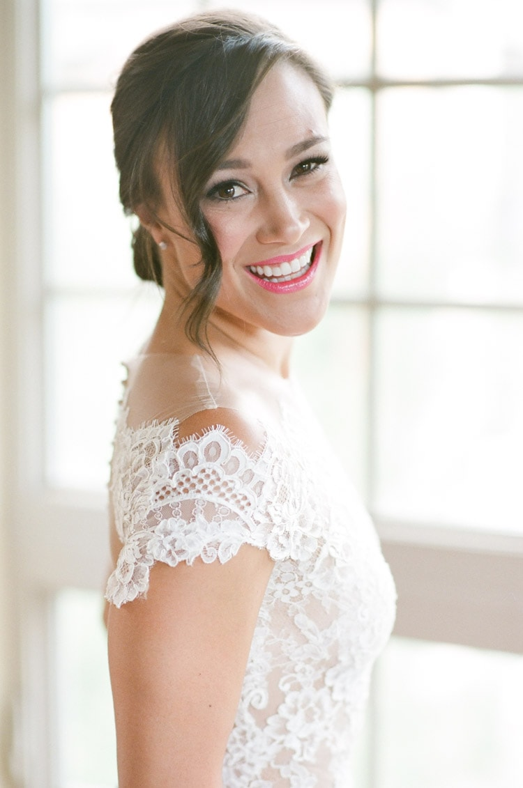 Bride smiling during getting ready session in white wedding dress
