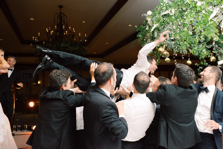 Groom being lifted up by people at reception