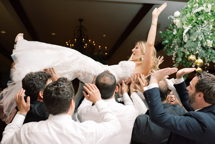 Bride being hoisted up by group of people
