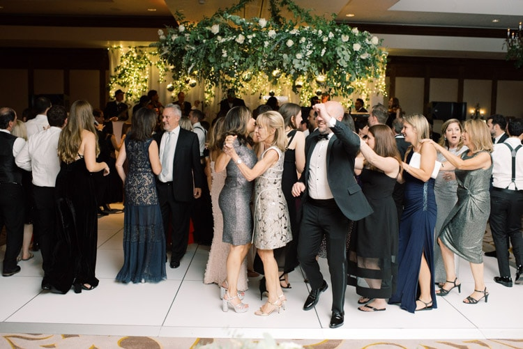 Dancing in the grand ball room with large greenery decoration hanging above