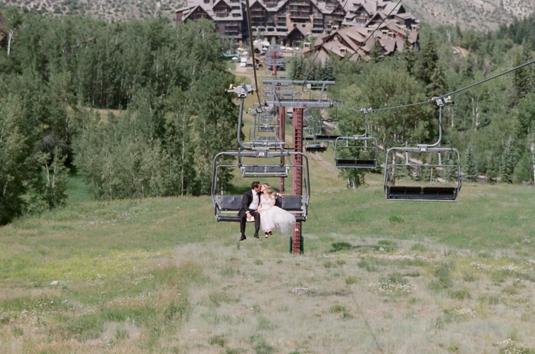 Wedding couple riding the gondola with the Ritz-Carlton resort in the background