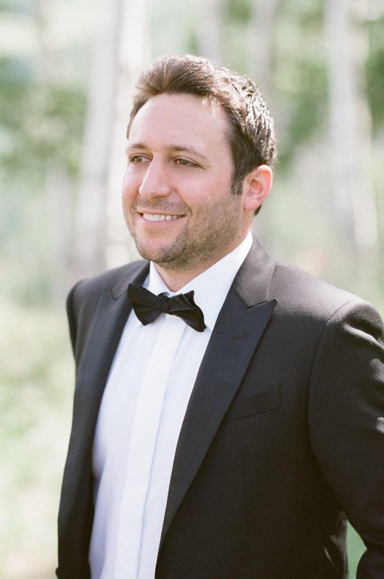Groom in black tuxedo smiling