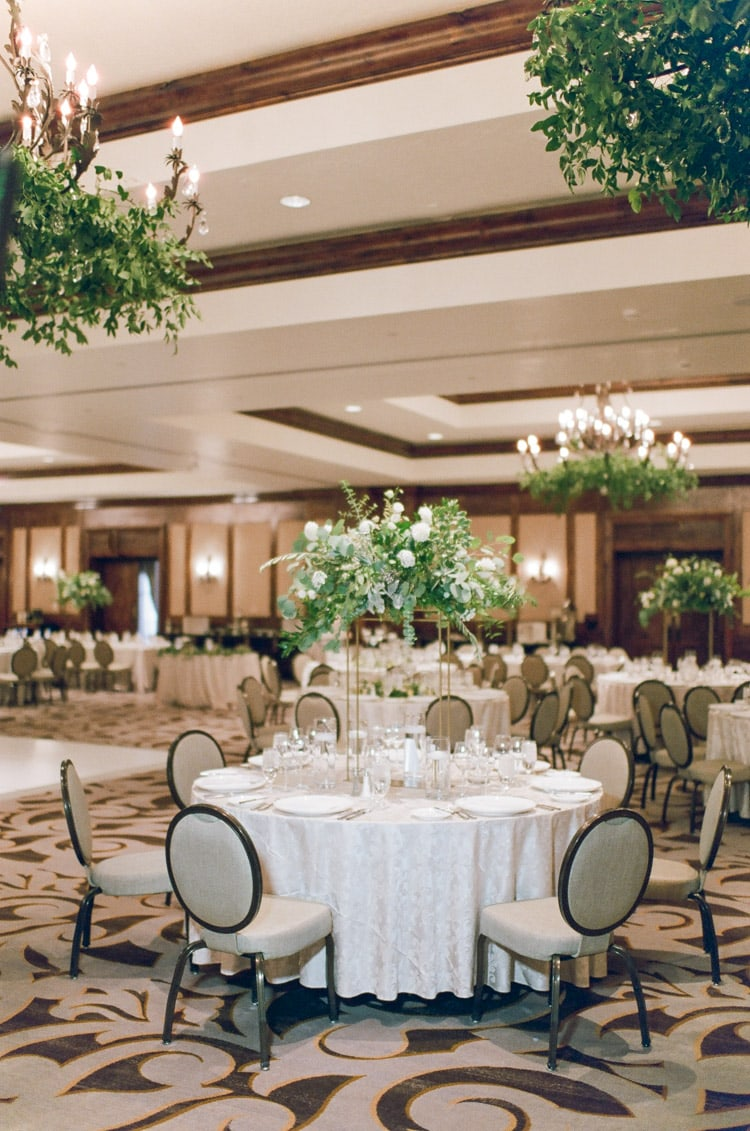 Wedding reception with white floral arrangements with greenery