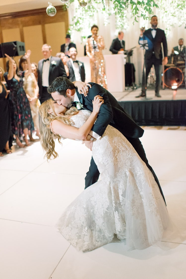 Wedding couple kissing after first dance on white dance floor