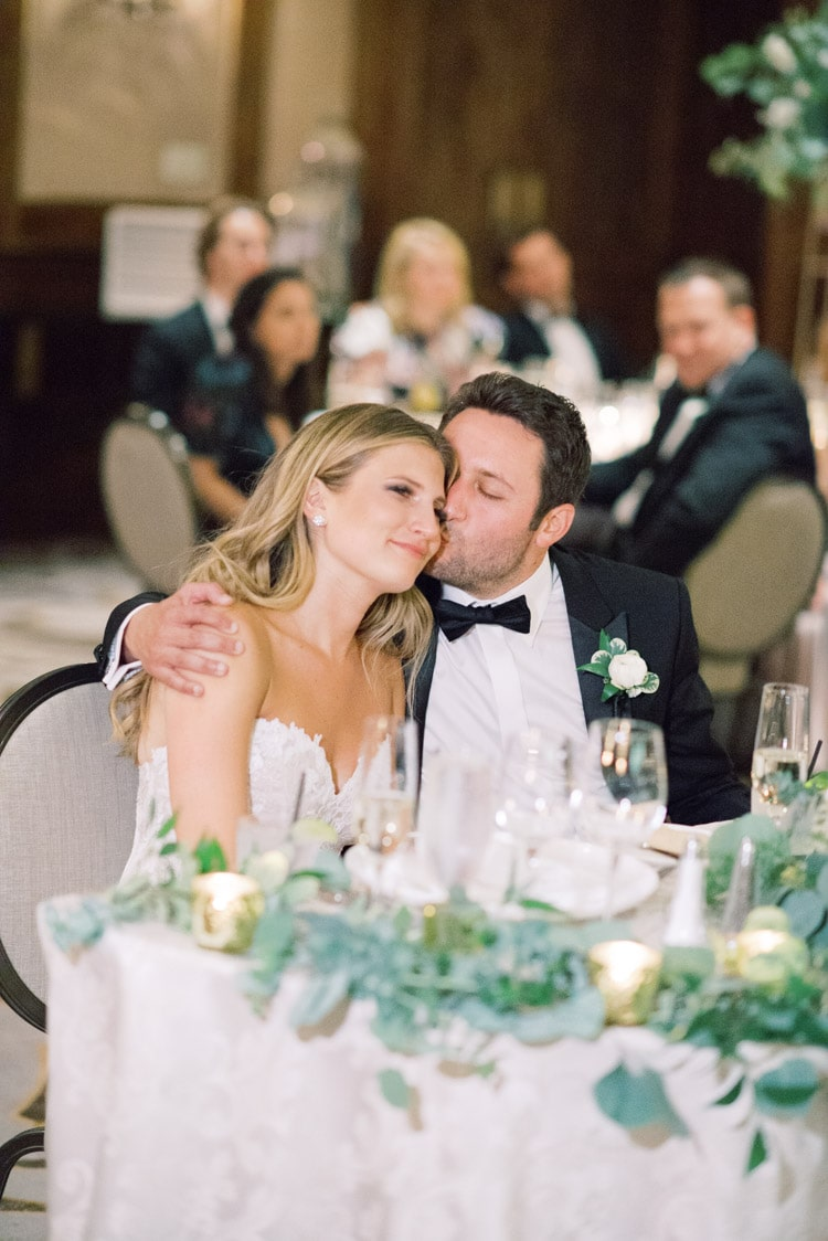Husband kissing his wife at wedding reception