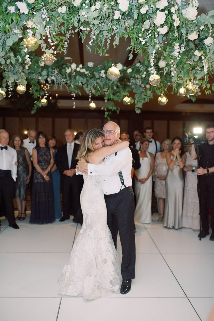 Bride slow dancing with father with huge floral halo above white dance floor